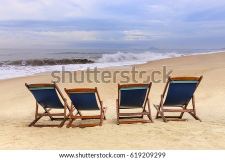 beach chairs on the sandy beaches for tourists to sit and relax with soft ocean waves breaking on beach in the early morning