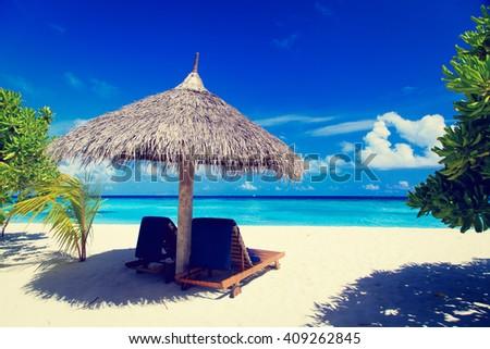 Beach chairs on the tropical beach - stock photo