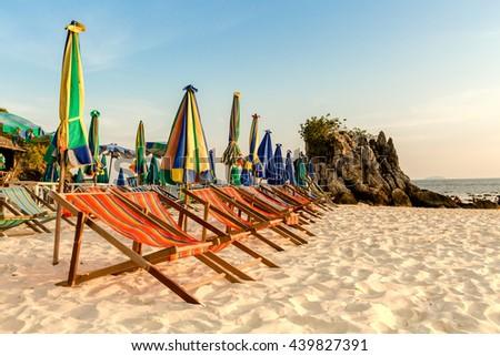 Beach chairs on the white sand beach. - stock photo