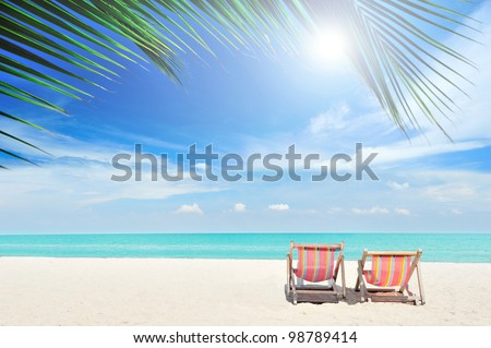 Beach chairs on the white sand beach, foreground with palm leaf, focus at chairs, with cloudy sky and sun