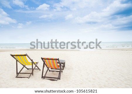Beach chairs on the white sand beach with beautiful cloudy blue sky - stock photo