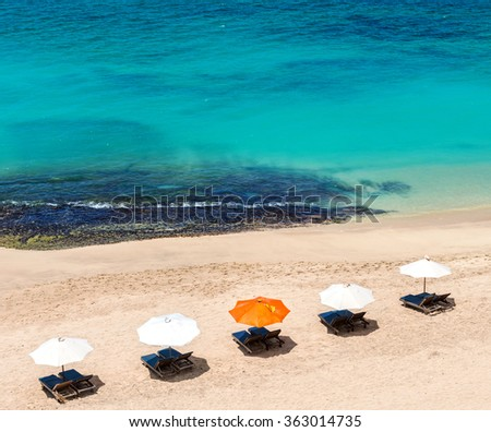 Beach chairs on the white sand beach with cloudy blue sky - stock photo