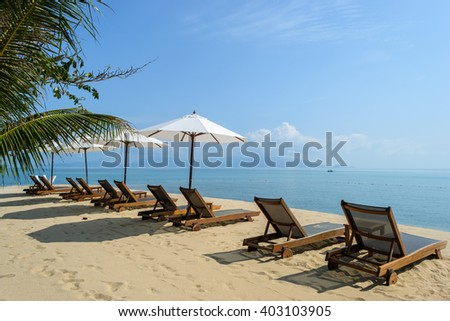 Beach chairs on the white sand beach with cloudy blue sky,Koh Samui in Thailand