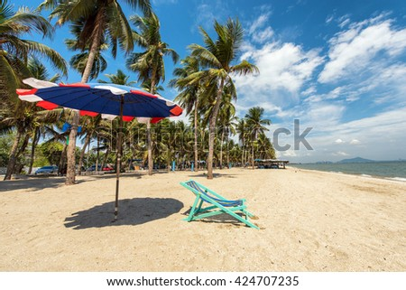 Beach chairs on the white sand under coconut tree beach with cloudy blue sky and sun  - stock photo