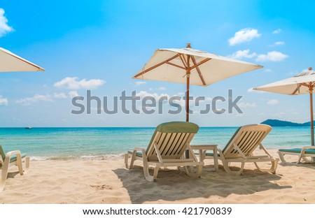 Beach chairs on tropical white sand beach - stock photo