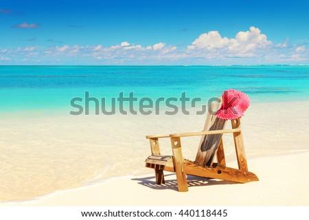 Beach chairs on white sand beach with cloudy blue sky and sun - stock photo