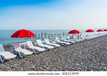 Beach chairs or beds and sun red umbrellas on the beach near sea - stock photo