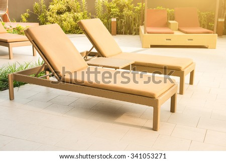 Beach chairs or pool beds beside swimming pool - stock photo
