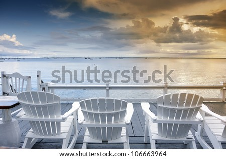 beach chairs overlooking tranquil ocean at sunset on old cape cod