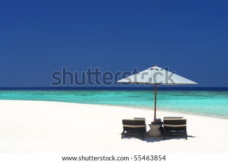 Beach chairs under an umbrella on a quiet stretch of pristine beach - stock photo