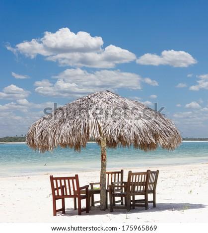 beach chairs under the shade of a palapa sun roof umbrella in Jericoacoara, Brazil - stock photo