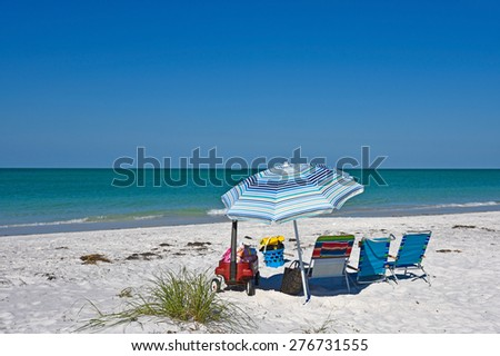 Beach Chairs, Wagon and Toys with an Umbrella on the Beach - stock photo