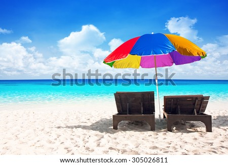 Beach chairs with colorful umbrella and beautiful sand beach - stock photo