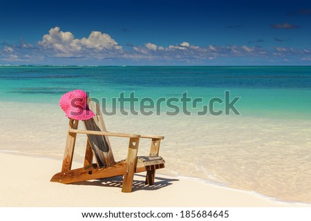 Beach chairs with pink hat  on white sandy beach  - stock photo