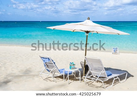 Beach Chairs with Towels and a Parasol on a Tropical White Sand Beach - stock photo