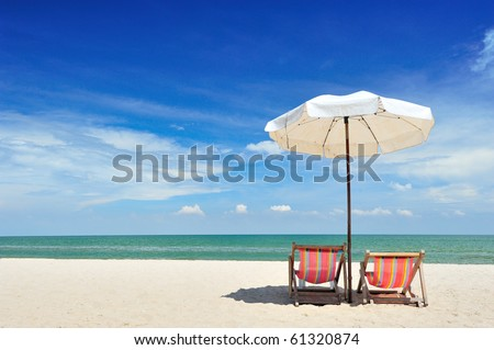 Beach chairs with umbrella and beautiful beach on a sunny day stock