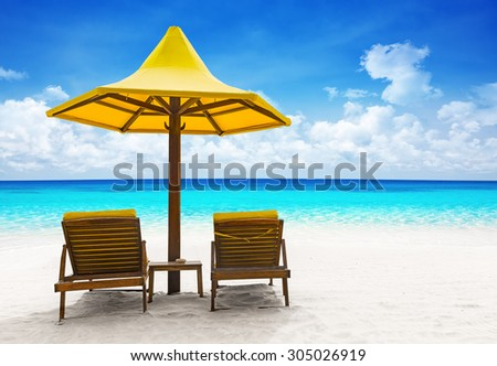 Beach chairs with umbrella and beautiful sand beach - stock photo