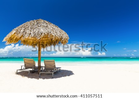Beach chairs with umbrella and beautiful sand beach in Punta Cana,  - stock photo