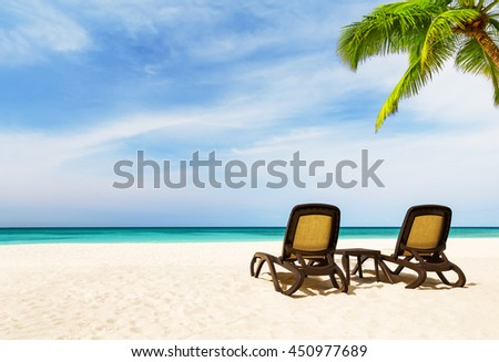 Beach chairs with umbrella and beautiful sand beach in Punta Cana, Dominican Republic - stock photo