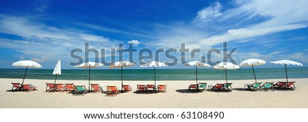 Beach chairs with umbrellas in panoramic view