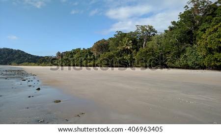 Beach coastline with daintree rainforest in the background, Cape Tribulation, Australia - stock photo