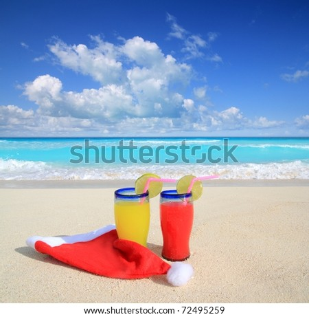 Beach cocktails with Santa christmas red hat winter vacation metaphor - stock photo