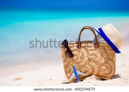 Beach consept - straw bag, hat, sunglasses and towel on white beach - stock photo