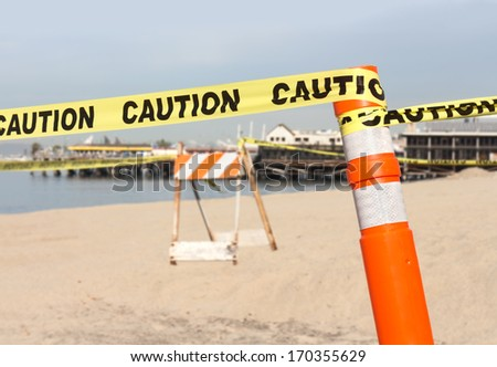 "Beach construction site warning in sand.Yellow ribbon with word ""caution"" tied to plastic orange post.Reflective white tape on post.Construction barricade,ocean,sky,sand,pier in blurred background."