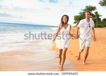 Beach couple walking on romantic travel honeymoon having fun running on vacation summer holidays romance. Young happy lovers, Asian woman and Caucasian man holding hands outdoors. - stock photo
