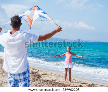 Beach cute girl with her father kite flying outdoor coast ocean - stock photo