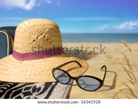 Beach Day straw hat and sunglasses on a beach - stock photo