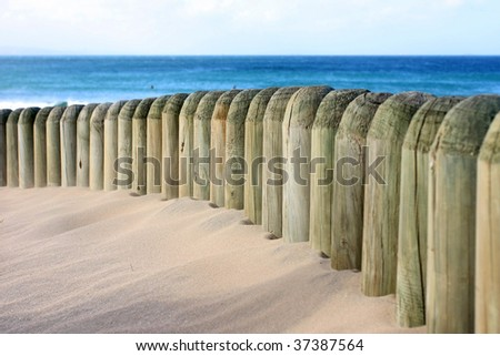 Beach dune and fence with the sea in the backgroung - stock photo