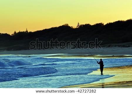 Beach Fishing at Sunset - stock photo