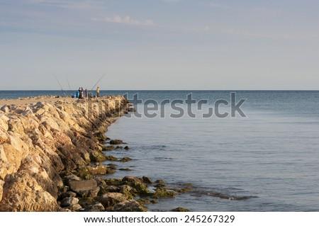 Beach fishing from the breakwater. Photo taken in Santa Pola, Valencian Community, Alicante,  - stock photo