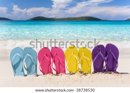 beach flip flops in rainbow color pattern on tropical sand