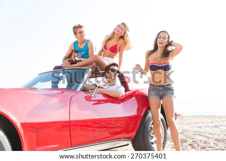 Beach friends together tourist portrait on the sand smiling happy - stock photo