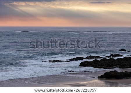 Beach from the north a Portugal just before sunset with interesting sky with some sunbeams - stock photo