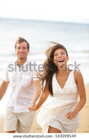Beach fun - couple laughing and running together during summer travel vacation holiday on beautiful golden beach. Joyful excited multi-ethnic couple, Asian woman and Caucasian man. - stock photo
