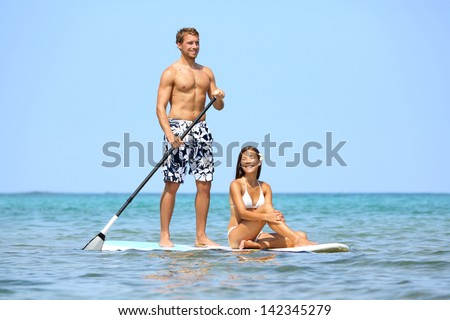 Beach fun couple on stand up paddleboard surfboard surfing together in ocean sea on Big Island, Hawaii Beautiful young multi-ethnic couple, mixed race Asian woman and Caucasian man doing water sport. - stock photo