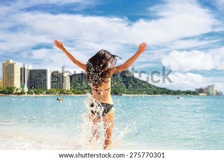 Beach fun - happy woman on Hawaii Waikiki vacation. Unrecognizable young adult from behind jumping of joy in water waves, arms up with diamond head mountain in the background, landmark of Honolulu. - stock photo