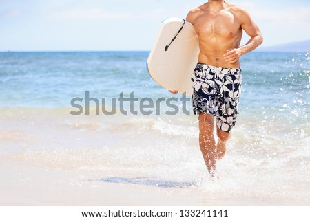 Beach fun surfer man running with body board. Fit fitness model doing water sport bodyboarding surfing. Photo from Kaanapali beach, Maui, Hawaii. - stock photo