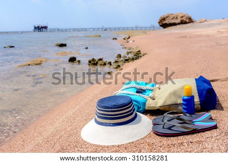 Beach gear arranged neatly at the waters edge on a sandy tropical beach with a sunhat, bag, slip slops, towel, sunglasses and suntan lotion conceptual of a summer vacation - stock photo
