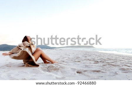 beach girl sits on the sand and opens her arms in a display of freedom and joy (panoramic large image with copyspace) - stock photo