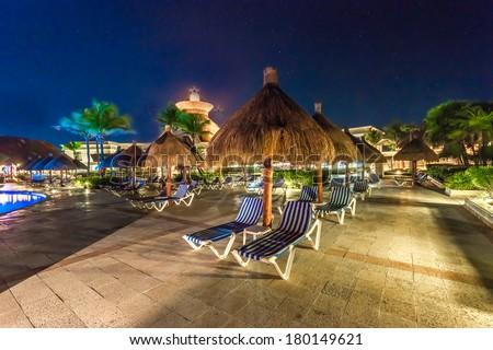 Beach, grass umbrellas and lounges at the swimming pool at luxury caribbean resort at night, dawn time. Bahia Principe, Riviera Maya, Mexico. - stock photo