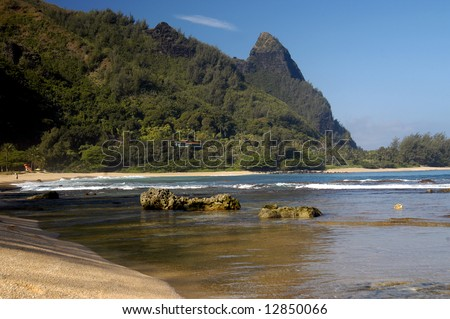 Beach has combination of mountainous backdrop with rugged peak, reef rocks, waves and sand.  Blue sky. - stock photo
