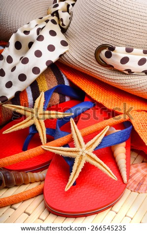Beach hat and bag with  towel and starfish on a wooden background - stock photo