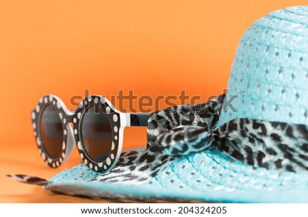 Beach hat and sunglasses with orange background - stock photo