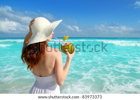 beach hat profile girl drinking a coconut fresh cocktail in tropical Caribbean sea - stock photo