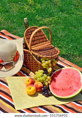 Beach hat, sun glasses, picnic basket with fruits and  bottle of wine on the green grass - stock photo