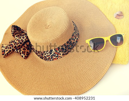 Beach hat, sunglasses and towel. Summer beach accessories.Toned vintage colors - stock photo